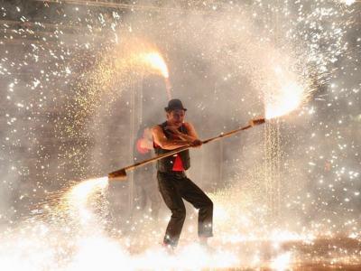 aktor na scenie miotający zimnymi ogniami, rozbłyskujące promienie i ogniki wirujące dookoła