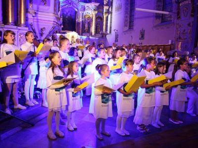 koncert w farze, chór dzieci w bieli w przestrzeni oświelonej niebieskim światłem
