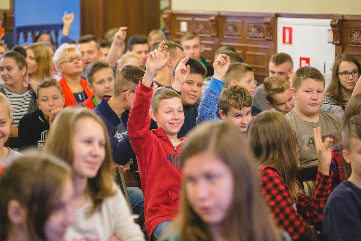 dzieci z uniesionymi rękami zgłaszają się do odpowiedzi