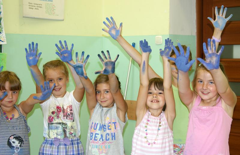 Lato na wsi 2013, na zdjęciu dzieci podczas zajęc z uniesionymi rękoma i dlońmi pomalowanymi na niebiesko