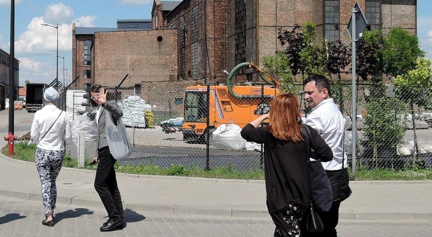 sześć osób przed starym budynkiem pofabrycznym