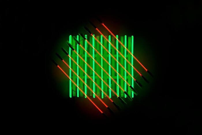 dwa kwadraty zrobione ze świecących rurek neonowy, nałożone na siebie i przekręcone względem siebie o 45 stopni, na czarnym tle