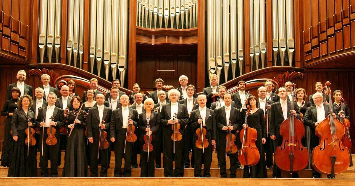 wieloosobowa grupa muzyków, stoją na scenie trzymając instrumenty