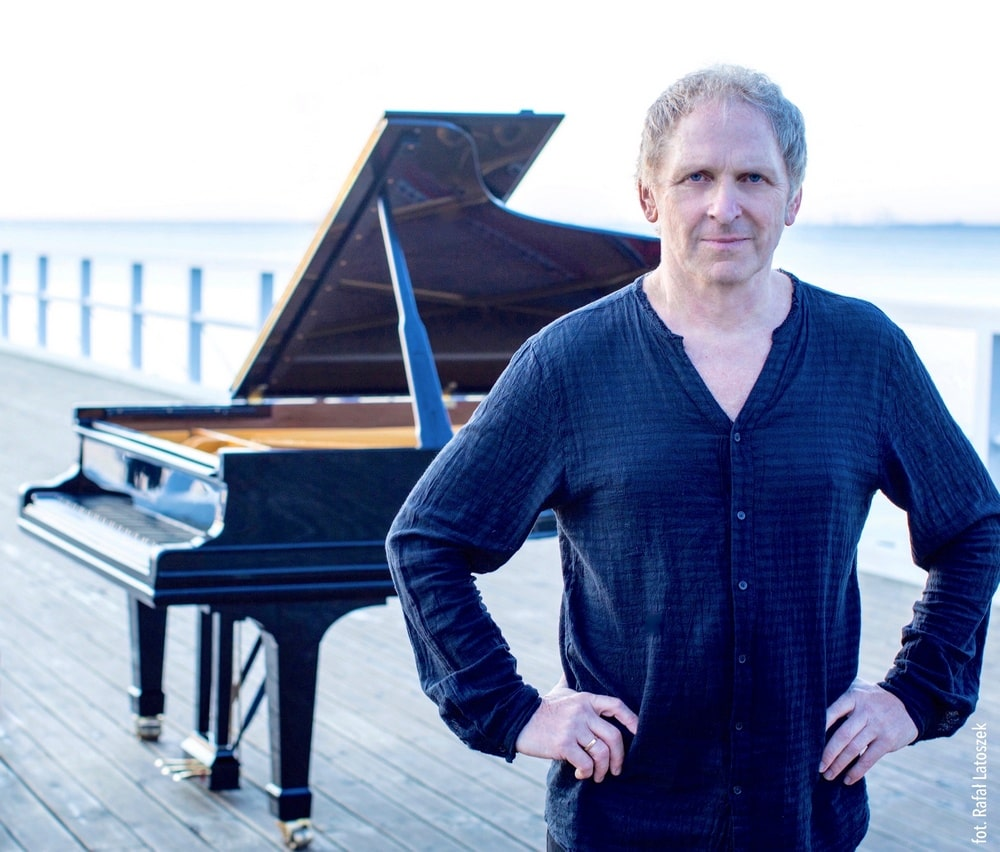 Artur Dutkiewicz stoi na tle fortepianu, na molo, w tle woda