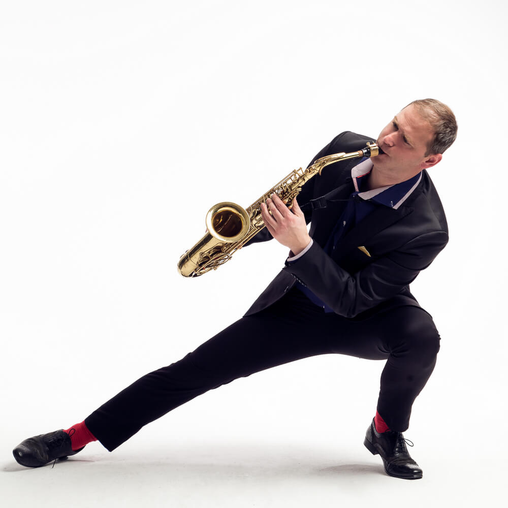 mężczyzna grający na saksofonie na ugiętych nogach