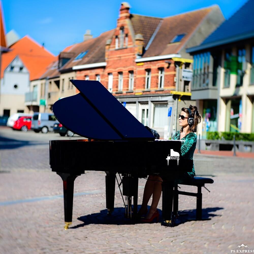 kobieta gra na fortepianie stojącym na rynku miasta