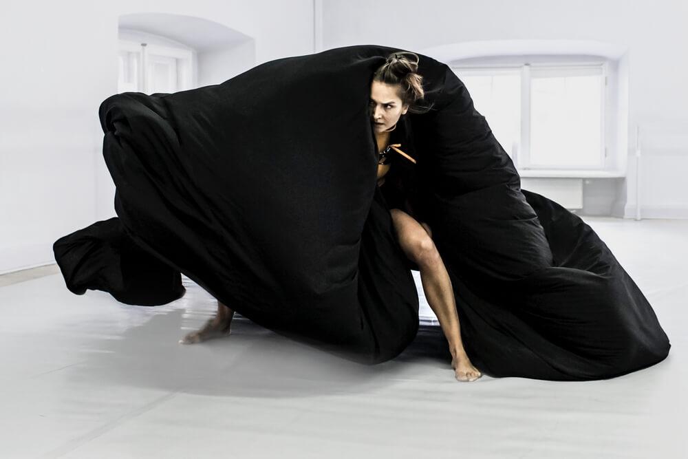 kobieta w ruchu okryta czarną peleryną