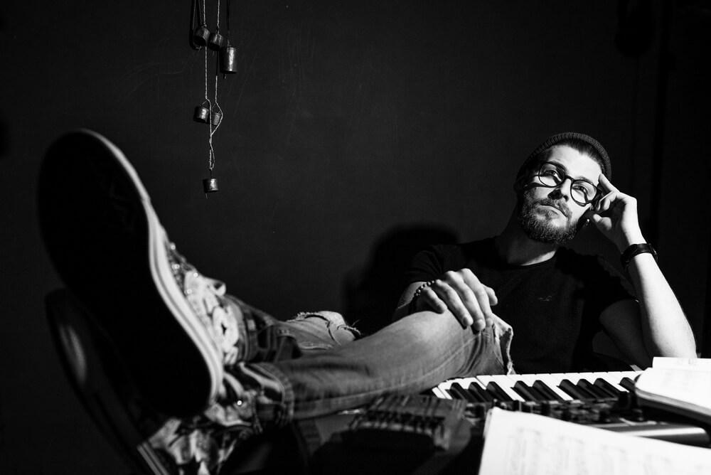 młody mężczyzna siedzi opierając nogi na klawiaturze