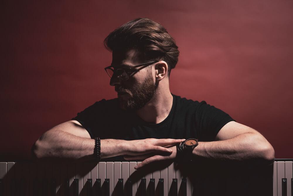 młody mężczyzna w okularach przy klawiaturze, patrzy w bok