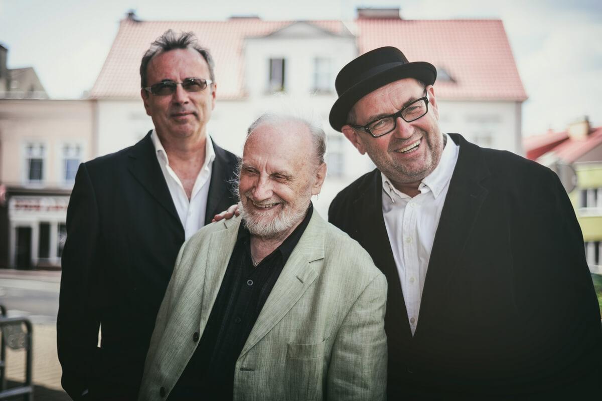 trzech mężczyzn stojących na tle budynku