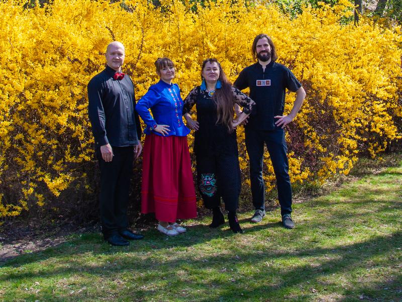 dwie kobiety i dwóch mężczyzna stoją na tle krzewu o żółtych liściach