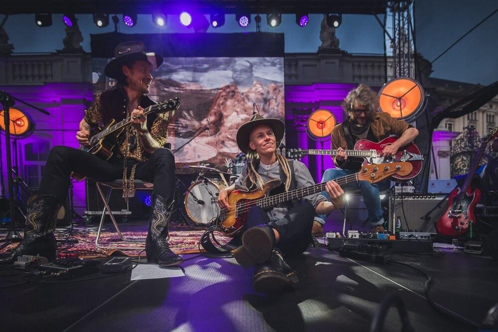 trzech muzyków z gitarami na scenie