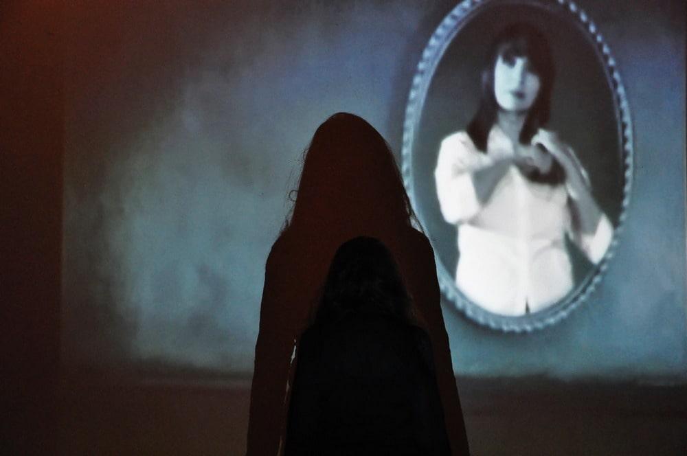 na pierwszym planie ciemna sylwetka kobiety w tle owalna fotografia kobiety
