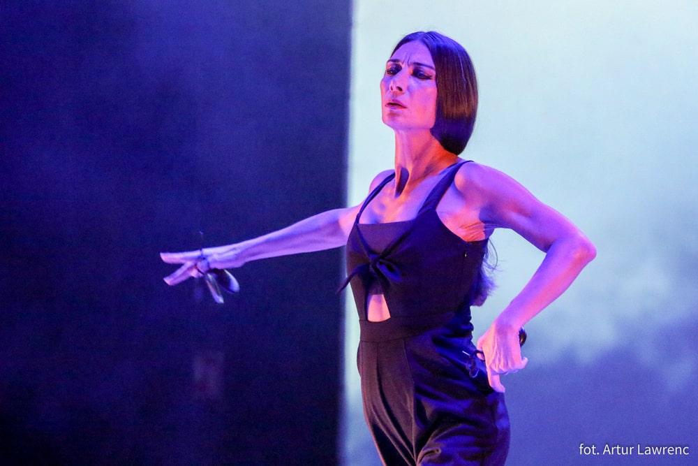 małgorzata matuszewska w czarnym kostiumie, stoi z wyciągniętą prawą ręką