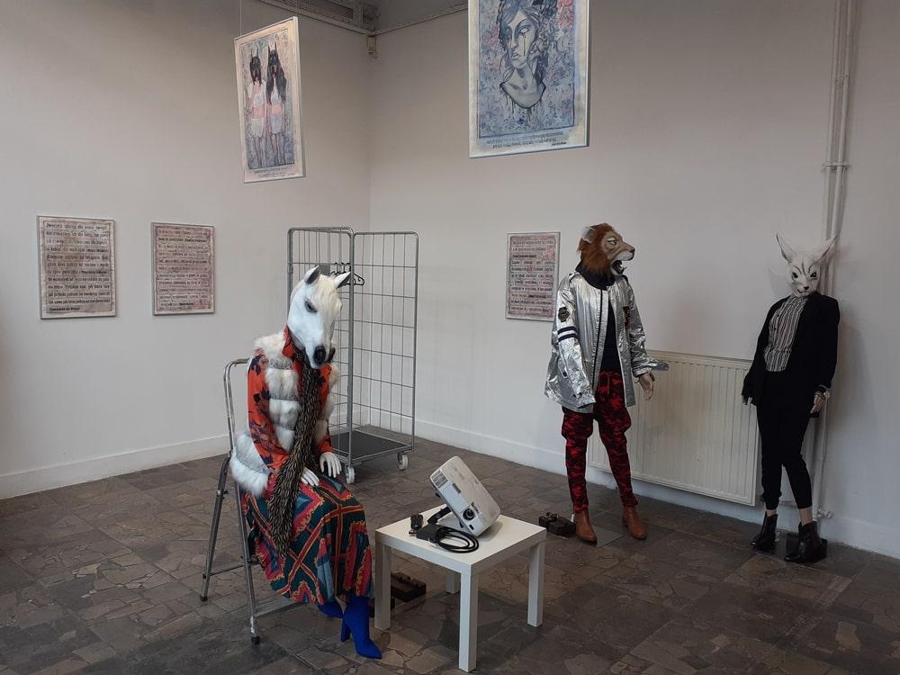 fotografia z wnętrza galerii xx1: trzy manekiny w ludzkich ubraniach z głowami konia, lwa i królika
