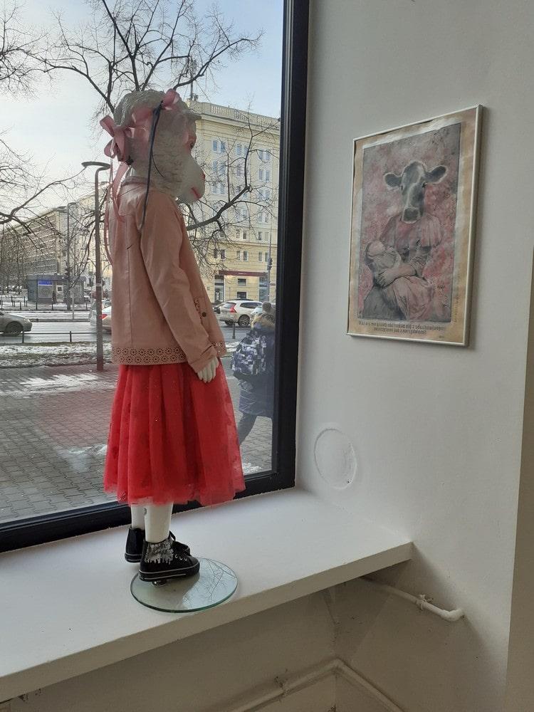 fotografia: manekin w ubraniu dziewczynki z głową owcy stoi na parapecie okna galerii