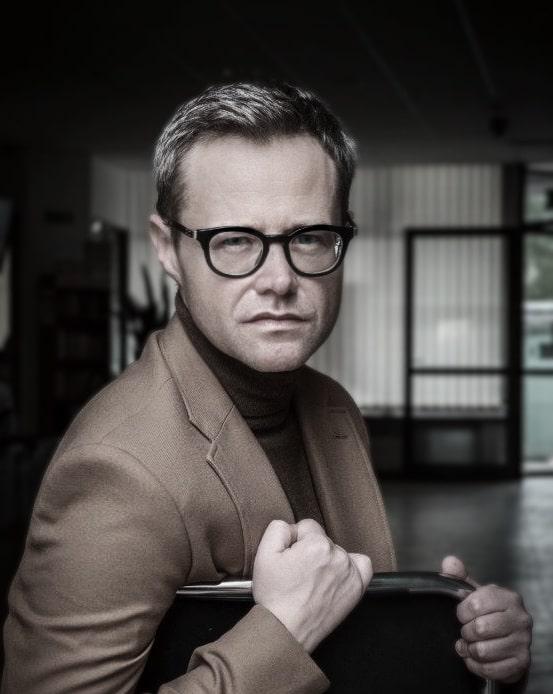 fotografia mężczyzna w okularach siedzi na krześle, patrzy w obiektyw