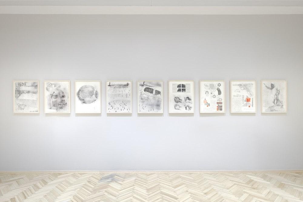 fotografia ściany w galerii na której wisi dziewięć obrazów z wystawy