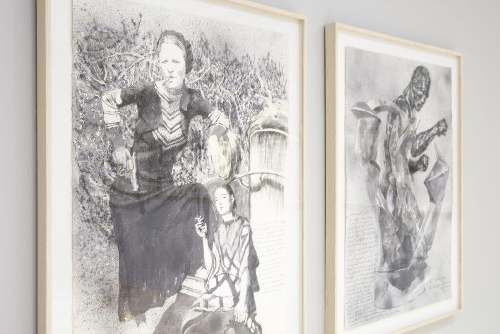 dwa obrazy na ścianie pierwszy to kobieta z pistoletem oparta o maskę samochodu