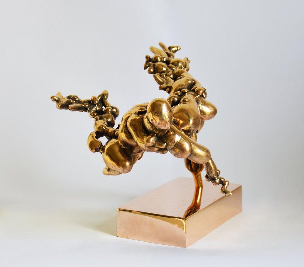 rzeźba: złote obłe kształty połączone ze sobą