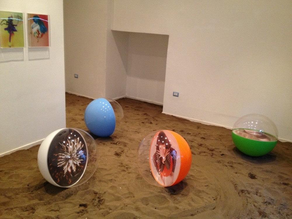 kompozycja przestrzenna: cztery półprzezroczyste kule na piasku