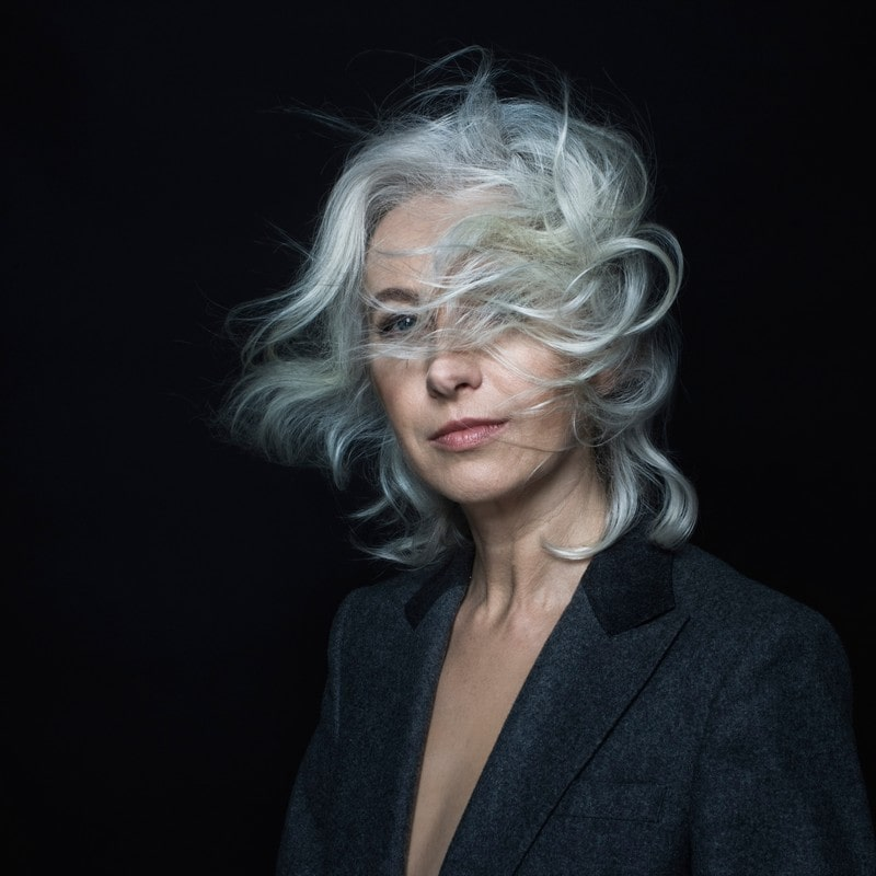 fotografia, portret: Manuela Gretkowska z rozwianymi włosami, na ciemnym tle