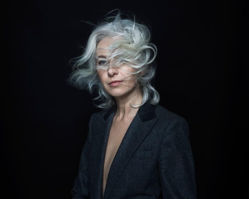 fotografia: na ciemnym tle manuela gretkowska, w ciemnej marynarce, włosy przesłaniają twarz