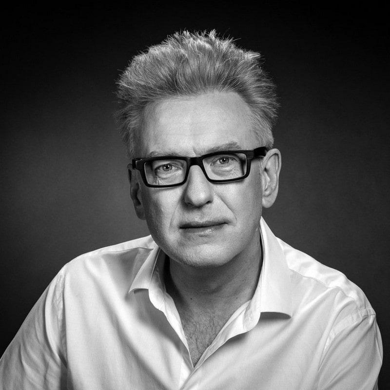 fotografia portret czarno biały: Mariusz Szczygiel, mężczyzna w średnim wieku, w koszuli i okularach