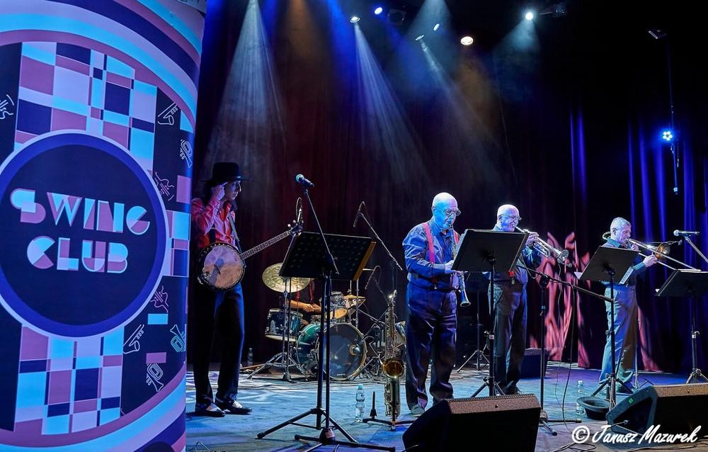 fotografia: grupa muzyków z instrumentami na scenie, obok plakat Swing Club