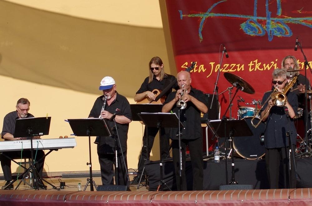 fotografia: grupa muzyków z instrumentami na scenie plenerowej, grają oświetleni słońcem