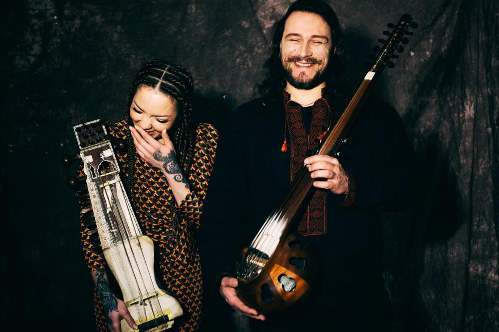 fotografia: ifi ude i bart pałyga stoją obok siebie, trzymają w rękach instrumenty, uśmiechają się