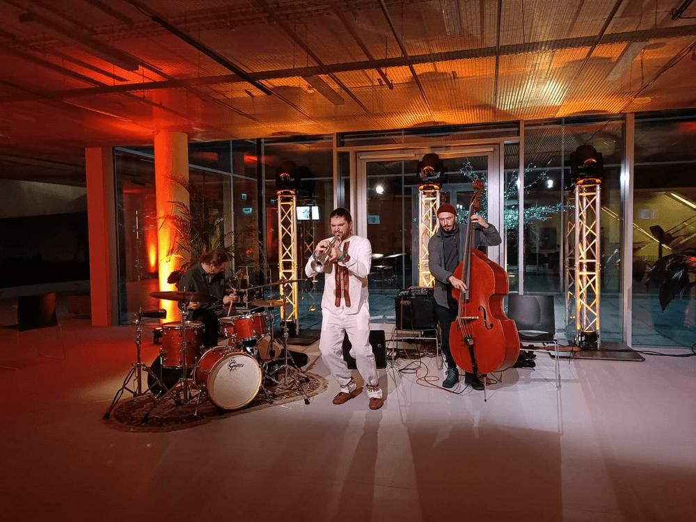 fotografia: trzech muzyków na scenie perkusista, trębacz i basista
