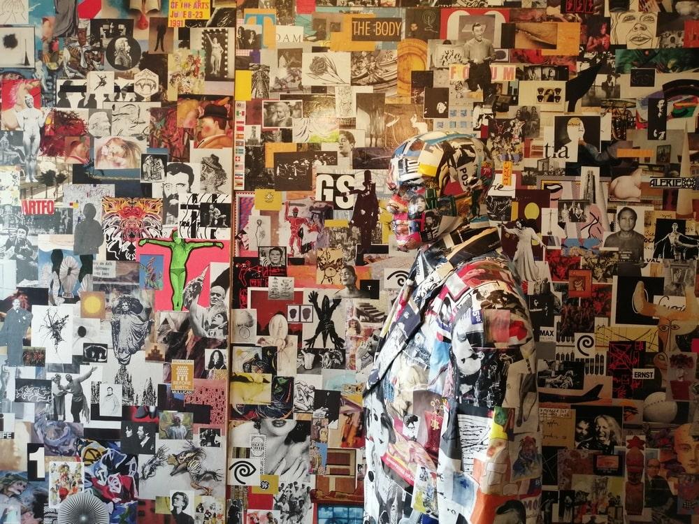 fotografia: manekin człowieka oklejony wycinkami prasowymi i fotografiami, na tle ściany podobnie oklejonej, wtapia się w tło