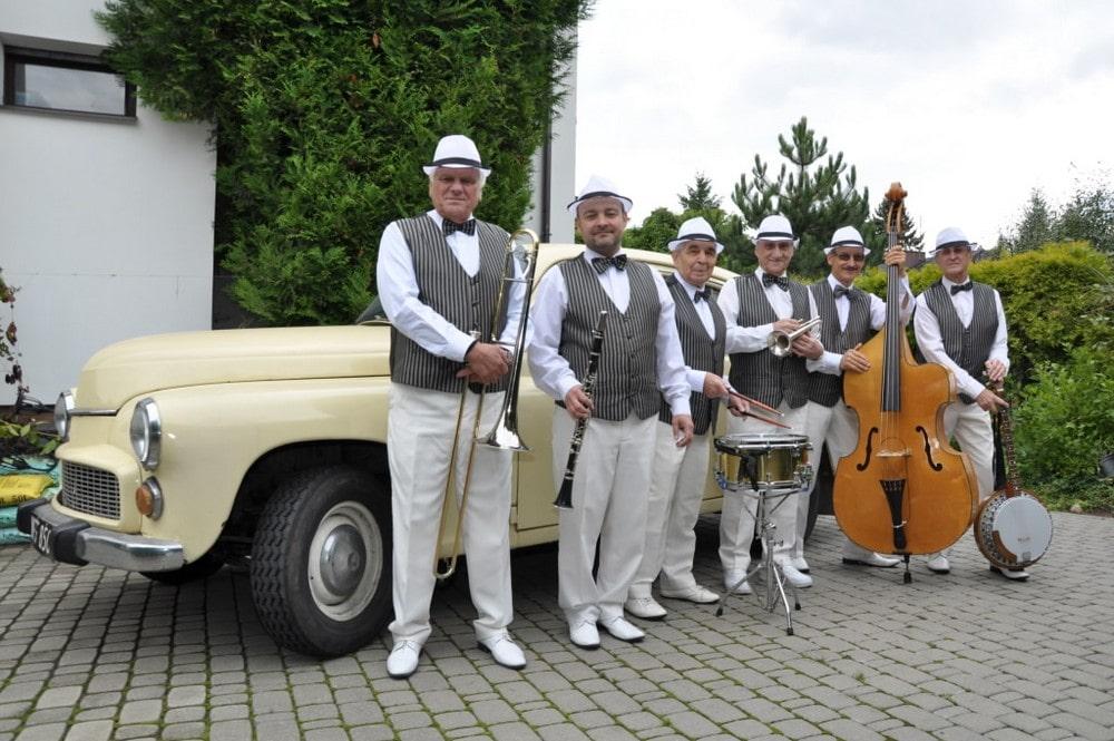 fotografia: sześciu mężczyzn w jednakowych garniturach, trzymają w rękach instrumenty muzyczne, stoją przed starym samochodem marki Warszawa
