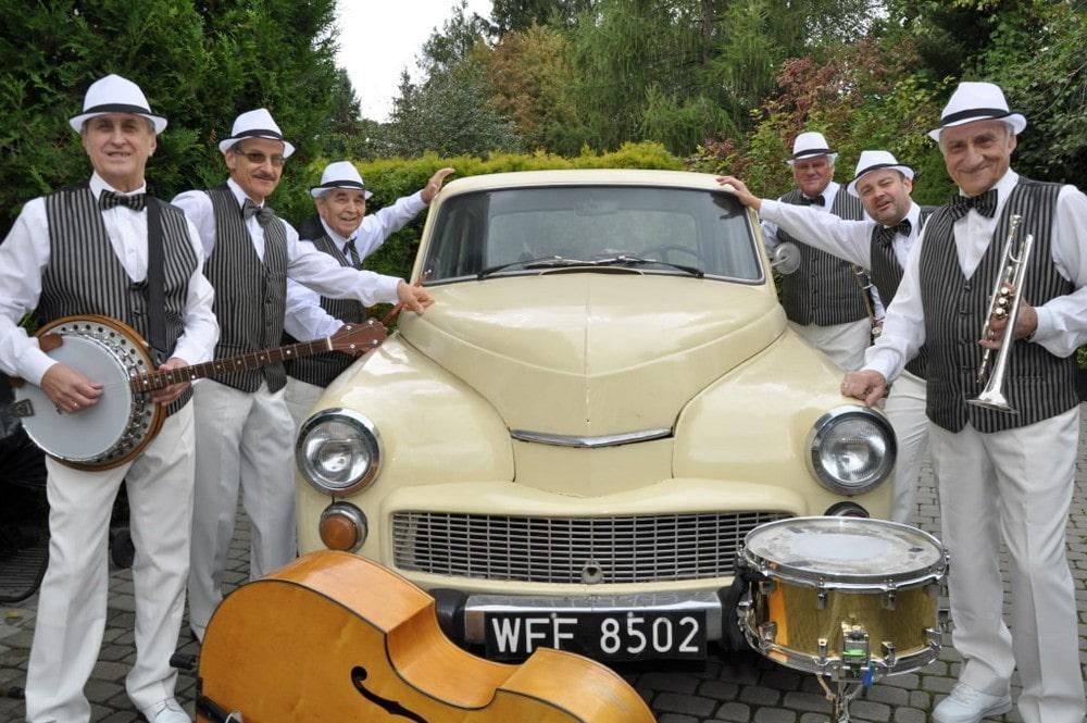 fotografia: sześciu mężczyzn w jednakowych garniturach, opiera się o stary samochód marki warszawarym samochodem marki Warszawa