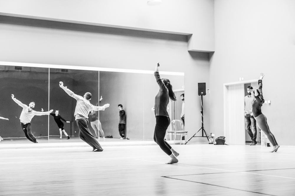 fotografia czarno biała: kilka osób ćwiczy w sali baletowej przed lustrem między innymi mężczyzna w pochylony z podniesionymi rękami