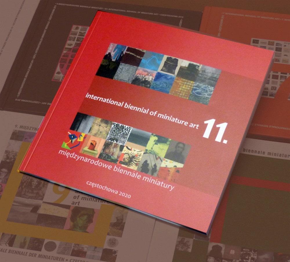 zdjęcie okładki katalogu wystawy, czerwone tło i biały napis 11 międzynarodowe biennale miniatury