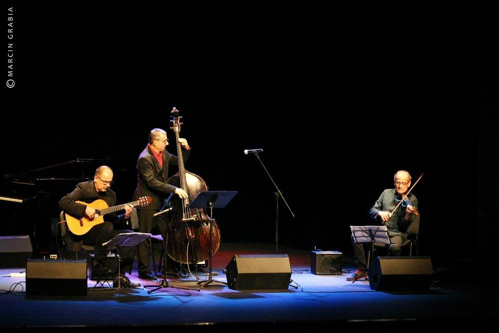 fotografia: trzech muzyków na scenie - gitarzysta, basista i pianista