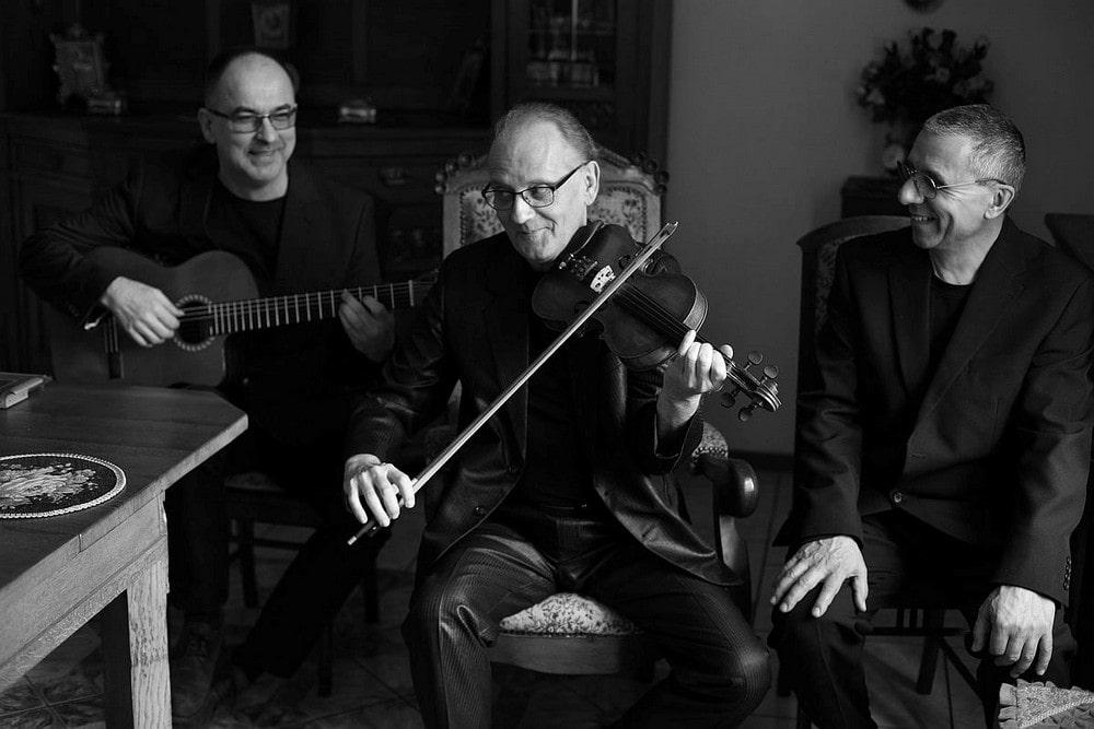 fotografia czarno biała: trzech mężczyzn siedzi obok siebie. środkowy gra na skrzypcach