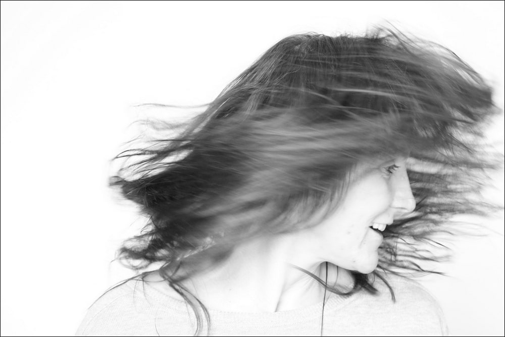 fotografia: czarno biały portret anny piotrowskiej - twarz z profilu, częściowo zasłonięta włosami