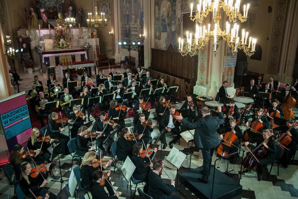 Fotografia: monumentalne wnętrze kościoła w Nasielsku, publiczność i orkiestra symfoniczna sfotografowana z góry