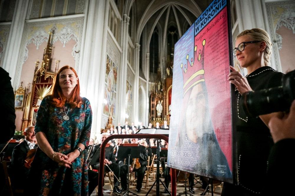 Małgorzata Kalicińska stoi we wnętrzu kościoła, obok stoi Ewa Krzysik i trzyma portret Małgorzaty Kalicińskiej