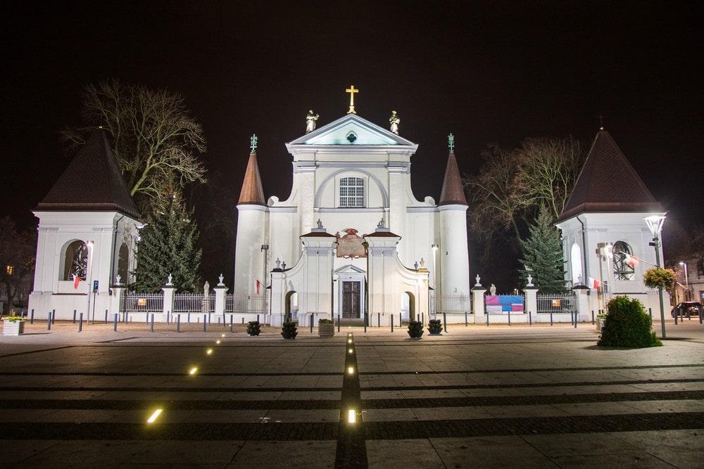 fotografia: biały front bazyliki w Węgrowie, sfotografowany nocą, podświetlony