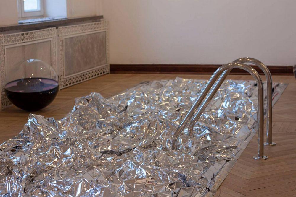 fotografia: na drewnianej podłodze rozłożona jest pofałdowana folia aluminiowa imitująca powierzchnię wody, z boku metalowe poręcze podobne do drabinki na basenie
