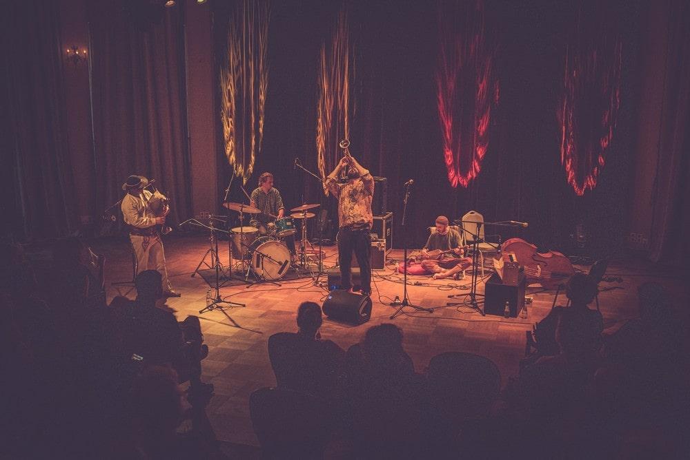 na zdjęciu widoczna publiczność podczas koncertu Piotr Damasiewicz Into. The Roots w MIKu, zespół w składzie Zbigniew kozera na kontrabasie, Piotr Damasiewicz na harmonium, Paweł Szpura na perkusji. Wydarzenie odbyło się w ramach projektu Space of Jazz.