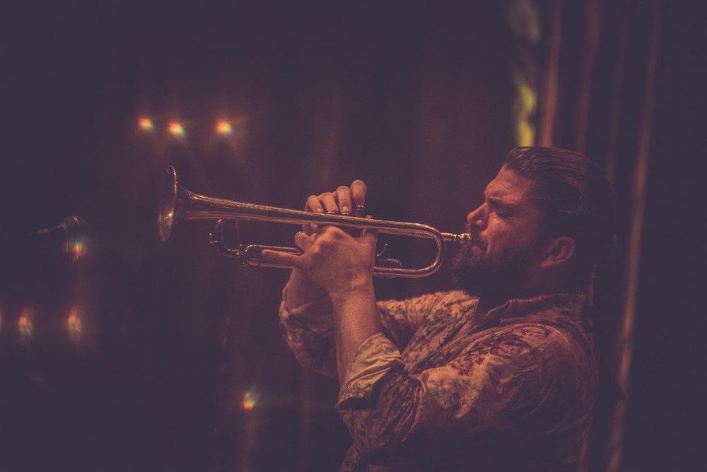 Piotr Damasiewicz gra na trąbce podczas koncertu Piotr Damasiewicz Into The Roots w MIKu. Wydarzenie odbyło się w ramach projektu Space of Jazz.