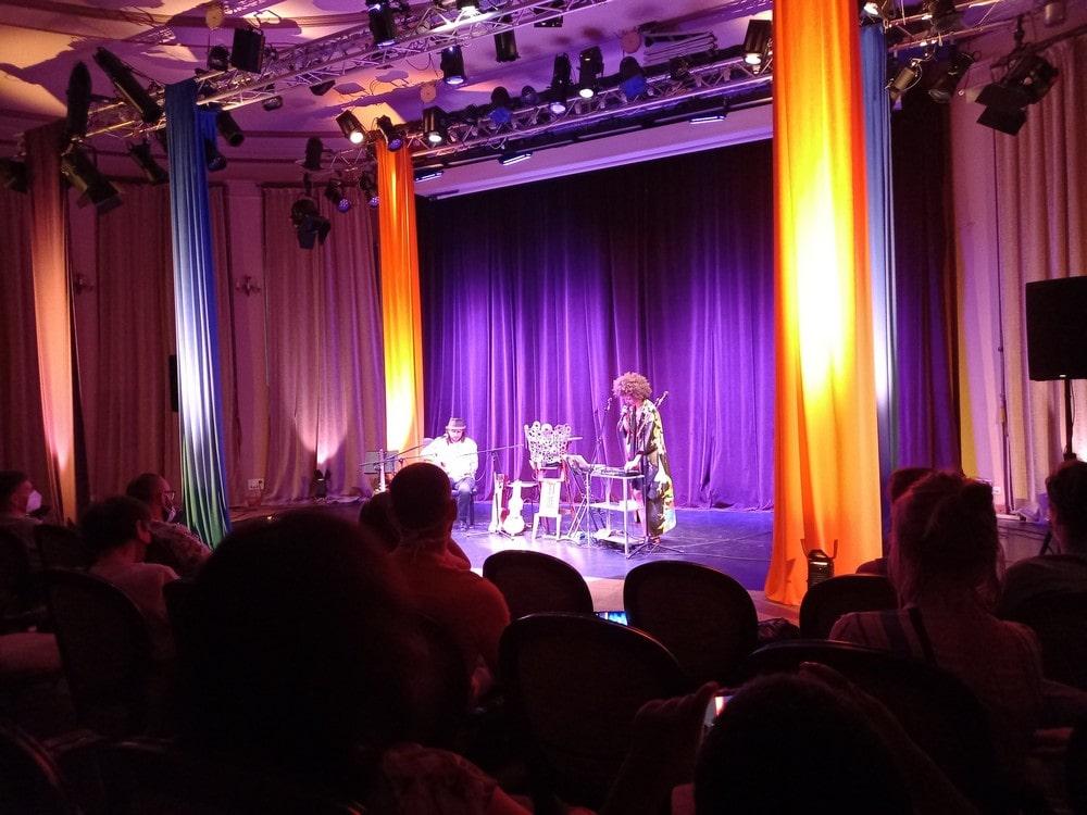 widok ogólny na scenę na której stoi ifi ude i bart pałyga. na pierwszym planie publiczność