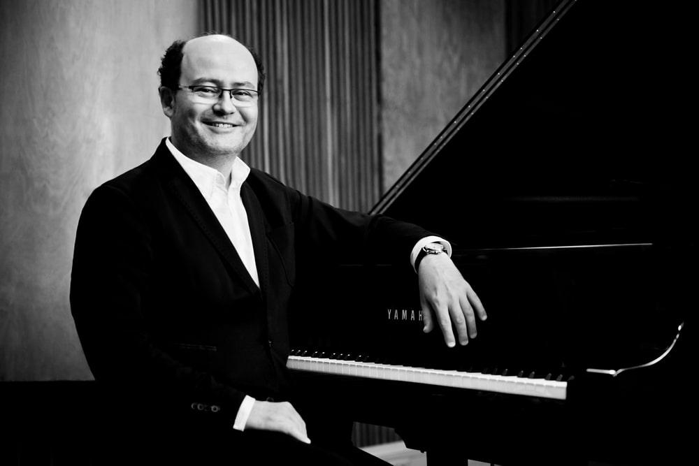 fotografia: Filip Wojciechowski muzyk mężczyzna w garniturze siedzący przy fortepianie