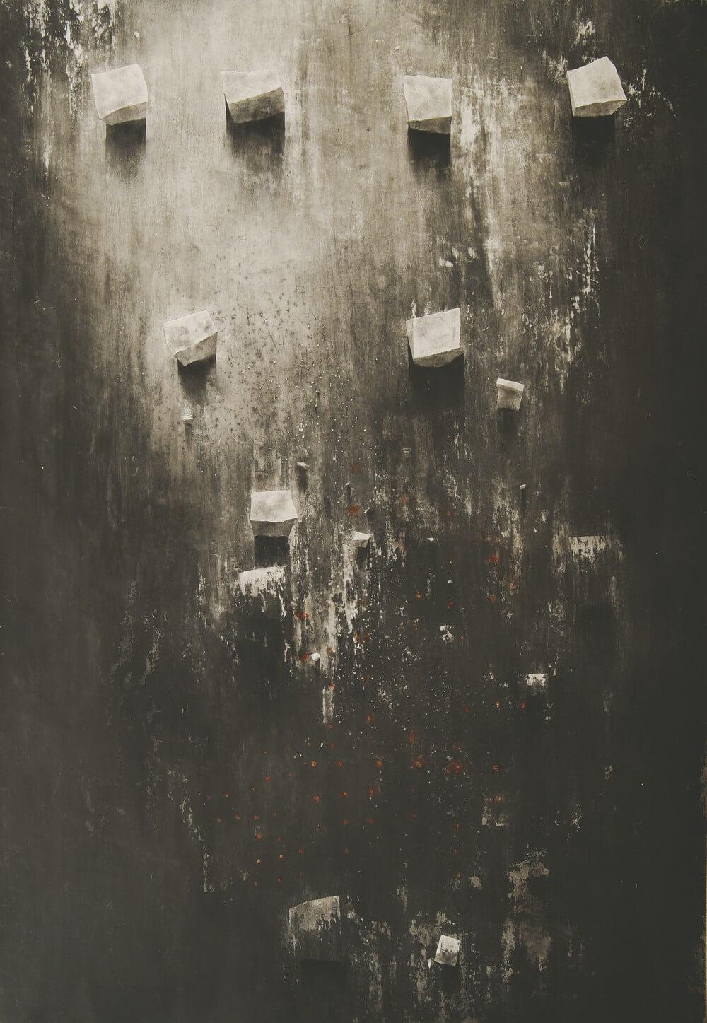 abstrakcja: tło ciemnoszare i jasnoszare, na jasnoszarym kilka brył, nieforemnych sześcianów