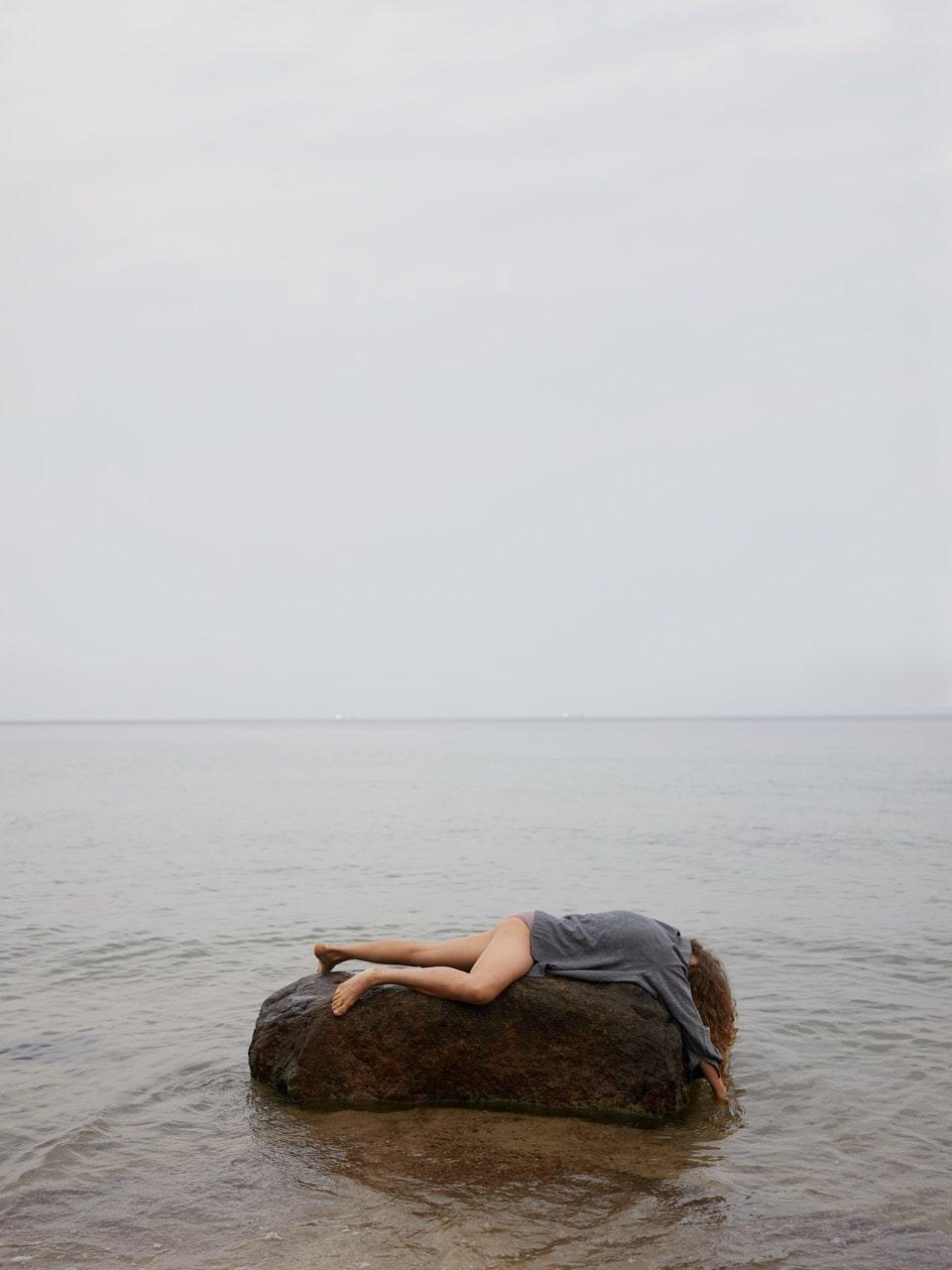 fotografia: kobieta leżąca na kamieniu, twarzą do dołu, kamień leży w wodzie